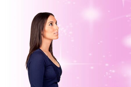 Mystical girl lookin-up isolated on a over pink background with stars photo