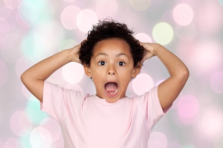 sparkled: Surprised latin child isolated on a pink sparkled background
