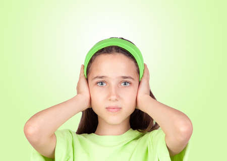 deafening: Frightened girl covering her ears isolated on a green background