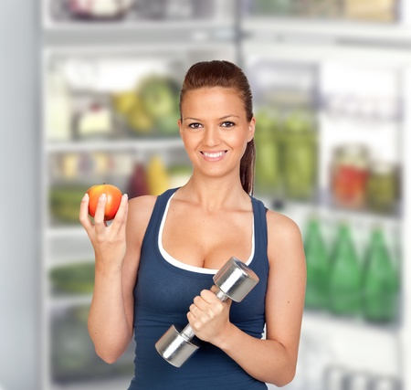Attractive girl eating a apple of de fridge after training photo