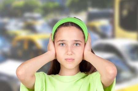 Frightened girl with ears plugged with many cars of background