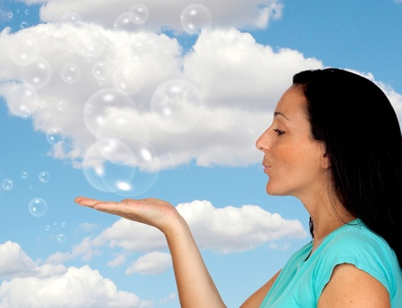 Adorable woman blowing bubbles with a blue sky of background photo
