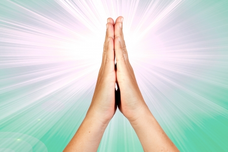 Hands clasped in prayer with rays of light on green background Stock Photo