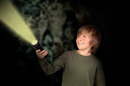 dark blond: Child with a flashlight looking for something on darkness background Stock Photo