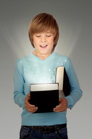 preteen boy: Gar�on pr�adolescent, avec un livre �clair� isol� sur fond gris Banque d'images