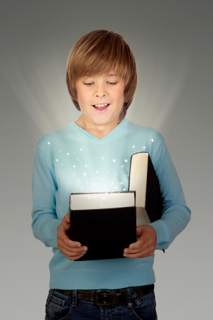 Preteen boy with a lighted book isolated on gray background photo