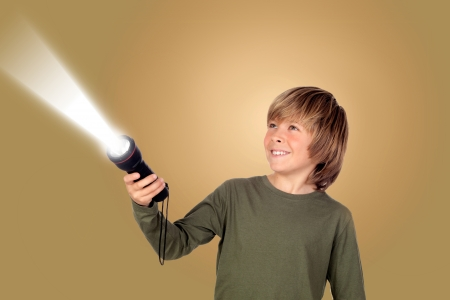 Child with a flashlight looking for something on brown background