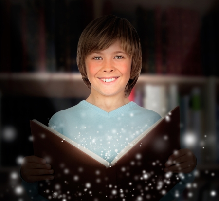 Preteen boy with a lighted book reading in the library Stock Photo - 18417545