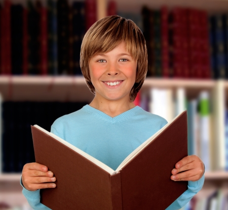 Preteen boy with a big book reading in the library Stock Photo - 18448138