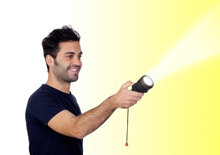 iluminate: Attractive men in black with a flashlight looking for something on yellow background