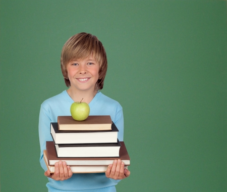 Preteen boy with a many books with a green blackboard for backgrond Stock Photo - 18522277