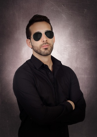 Young bearded businessman with sunglasses on a over gray and irregular background photo