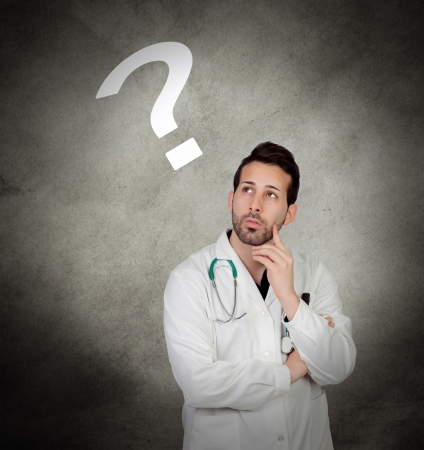 Pensive young doctor on a over irregular and gray background photo