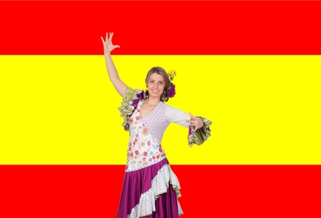 Spanish girl dressed in traditional costume Andalusian dancing on a over red and yellow background photo