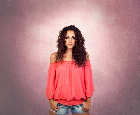 Brunette girl with a pink sensual shirt over a irregular background photo