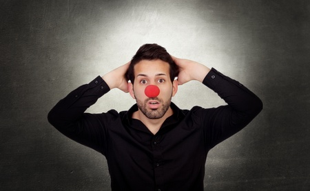 Astonished businessman with clown nose on a over gray and irregular background photo