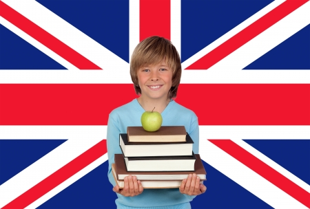 Happy Boy Holding Stack Of Books With Apple Against British Flag photo