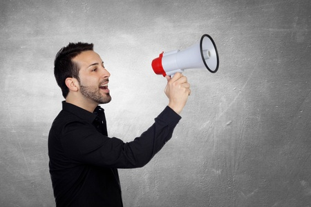 Young Man Shouting Through Megaphone Over Gray Background photo