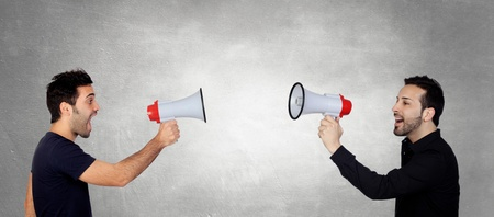 two people talking: Two Young Men Shouting Through Megaphone In Front Of Each Other Stock Photo