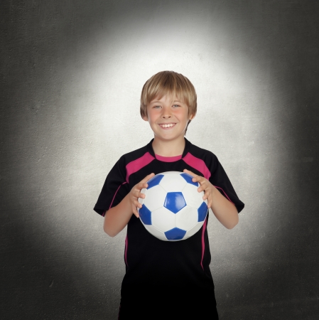 Preteen with a uniform for play soccer with a gray background photo