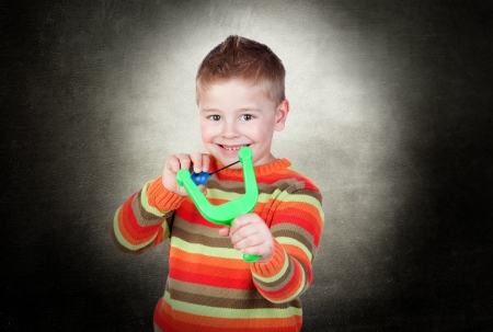 Portrait Of A Happy Boy Playing With Slingshot indoor photo