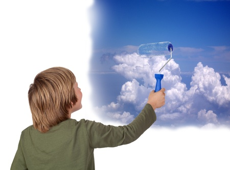 Adorable child painting a beautiful sky with a roller isolated on a over white background photo