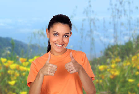 Attractive brunette woman saying Ok in field with beautiful flowers background photo
