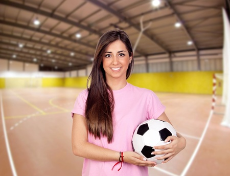 Atractive girl with a soccer ball in the sports center photo