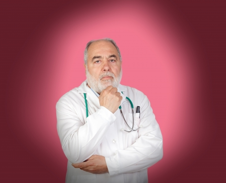 Thoughtful old doctor on a over pink background photo