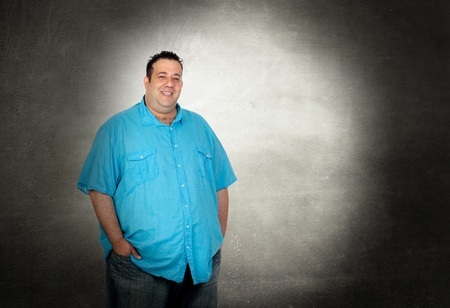 Happy fat man with blue shirt on a over gray background photo