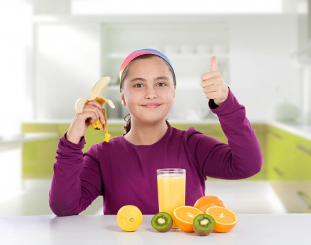 Adorable little girl eating fruits saying Ok on the kitchen photo