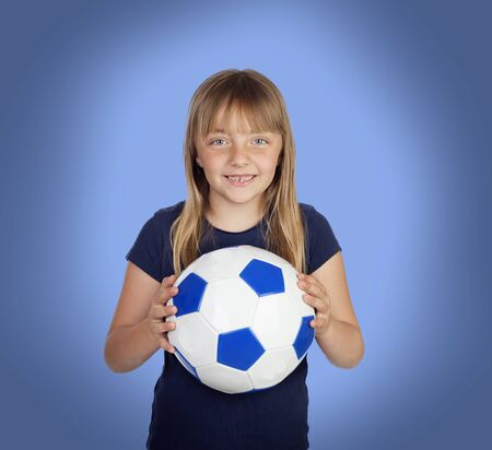 Adorable girl with a soccer ball on a over blue background photo