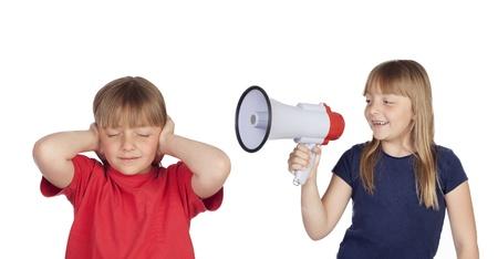 soeur jumelle: Petite fille avec le m�gaphone criant � sa s?ur jumelle isol� sur fond blanc Banque d'images