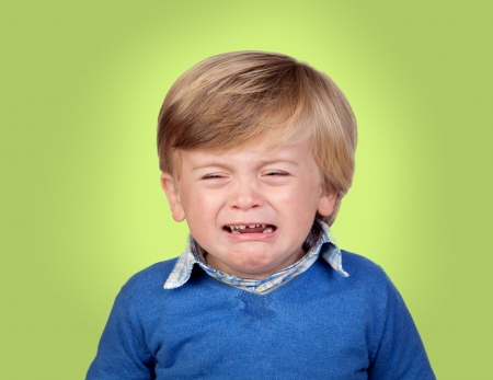 tantrums: Beautiful baby crying isolated on green background