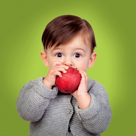 Adorable baby eating a red apple on a green background photo