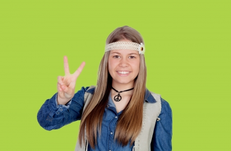 Pretty girl with hippie clothes making the peace symbol on green background photo