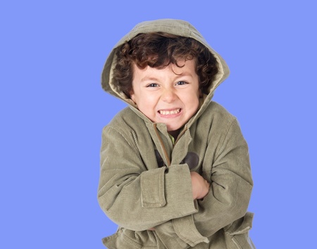 shivering: Funny little boy shivering with cold on a blue background