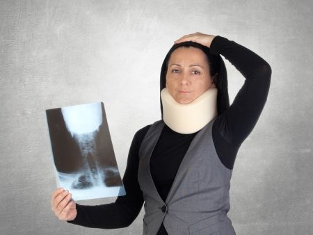 anatomically: Concerned woman with cervical collar and radiography on a gray background Stock Photo