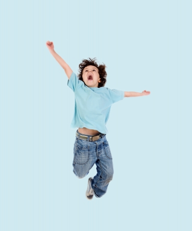 niños bailando: Adorable niño saltando sobre un fondo azul