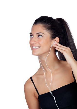 Attractive brunette girl looking up and listening to music isolated on a white background photo