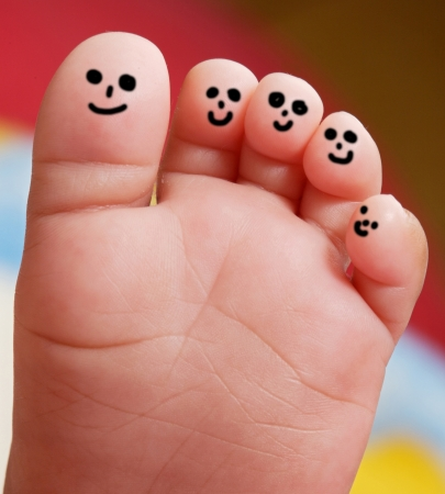 Nice foot of a baby with smiley faces painted toes