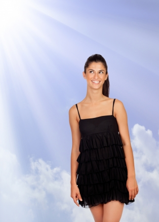 Attractive brunette girl with black dress looking up in a sunny day Stock Photo - 20310284