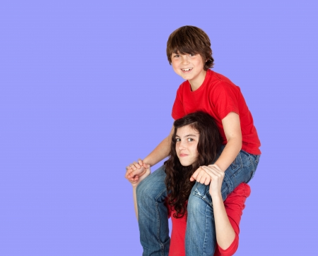brethren: Boy riding on his sister on a blue background Stock Photo