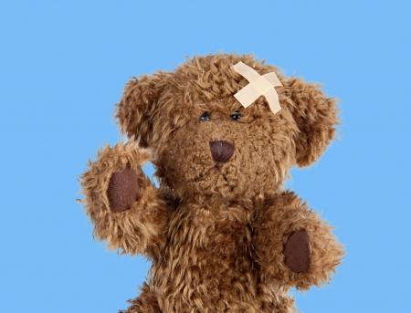 Nice teddybear with a band-air on a blue background
