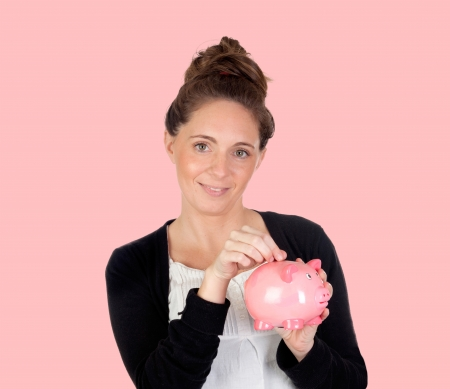 Attractive girl with money box on a pink background photo