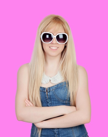 Young girl with sunglasses on a over pink background photo
