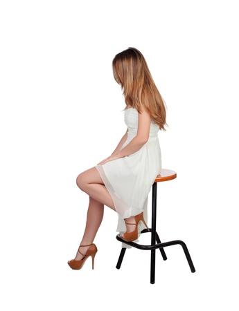 白い背景に分離したスツールに座っている魅力的なブロンド女性
