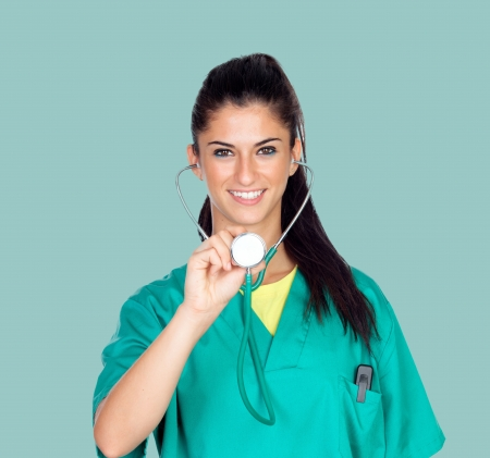 Attractive woman doctor with uniform on a green background