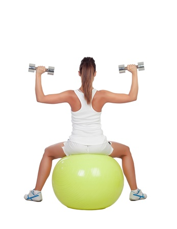 woman lifting weights: Attractive girl lifting weights sitting on a ball isolated on white background