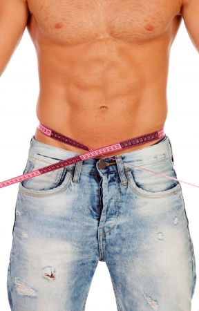 Man with perfect abs measuring his waist isolated on a white background photo